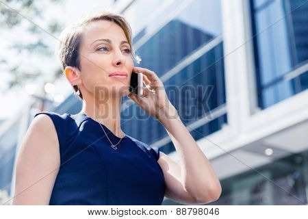 Businesswoman in city holding her mobile