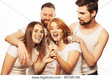 People, friendship  and leisure concept: group of young happy friends  having fun at karaoke, hipster style.Isolated on white.