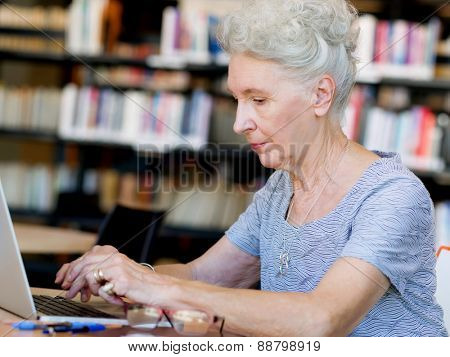 Elderly lady working with laptop