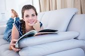 picture of couch  - Happy woman reading a magazine on couch at home in the living room - JPG