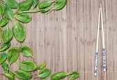stock photo of bamboo leaves  - green spinach leaves on a bamboo mat and bamboo chopsticks - JPG