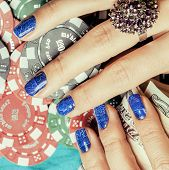 picture of nail-design  - hands of young caucasian woman with blue manicure at casino table close up - JPG