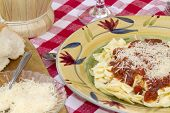 picture of glass noodles  - Italian pasta dinner served with Marinara sauce parmesan cheese over bow tie noodles accompanied by a glass of Chianti wine and bread - JPG