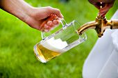 picture of draft  - man is tapping a draft beer from a barrel on a wedding - JPG