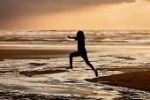 pic of leaping  - A girl in silhouette at sunset leaps into the creek on Nye Beach that flows into the ocean in Newport Oregon - JPG