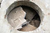 stock photo of orifice  - Concrete block with the manhole opening on the pile of damaged concrete blocks - JPG