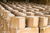 pic of loam  - Raw bricks covered with sawdust drying in the open air - JPG
