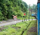 stock photo of railroad car  - Passenger train going across the railroad crossing with traffic lights and stop sign in the Carpathian Mountains  - JPG