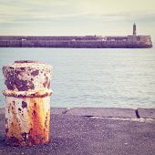 stock photo of bollard  - Rusty Bollard and the Old Lighthouse on the Atlantic Coast of Spain Retro Effect - JPG