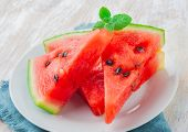 foto of watermelon slices  - sliced watermelon with mint leaf on a white plate - JPG