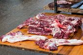 image of charcuterie  - Raw pork on wooden table at the market for sale - JPG