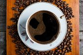 stock photo of coffee coffee plant  - Coffee beans and cup of coffee on wooden table - JPG