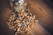 pic of walnut  - Walnut kernels and whole walnuts on rustic old wooden table glass jar - JPG