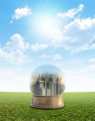 stock photo of smog  - A snow globe with a city surrounded by pollution and smog on a perfect flat green lawn against a blue sky with white clouds - JPG