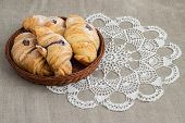 stock photo of doilies  - fresh breakfast with chocolate croissants on the woven basket on the table covered with grey linen cloth and decorated with white crochet doily - JPG