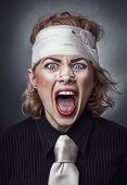 stock photo of scream  - Furious face of injured woman with bandage on head screaming - JPG