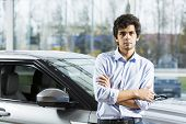 pic of showrooms  - Handsome young man standing besides car in showroom  - JPG