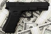 stock photo of handgun  - Handgun on american dollars close up shot - JPG