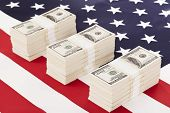 stock photo of 100 dollars dollar bill american paper money cash stack  - One hundred dollar bills on american flag - JPG