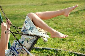 picture of barefoot  - barefoot young woman in dress on swing outdoor in park warm spring day - JPG