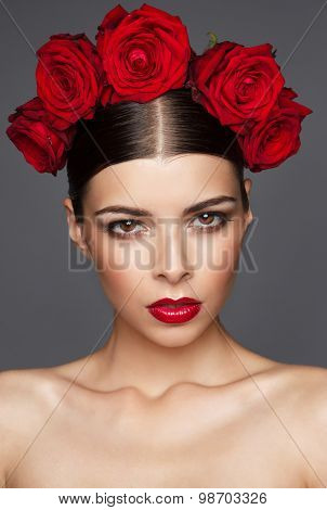 Portrait of beautiful woman with roses in hair