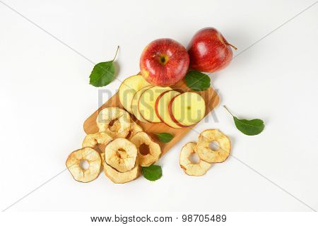 fresh red apples and apple rings on wooden cutting board