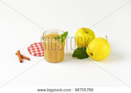 two yellow apples and glass of fresh apple sauce on white background