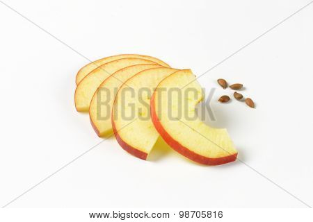 thin apple slices and seeds on white background