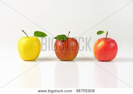 three washed apples in a row on white background