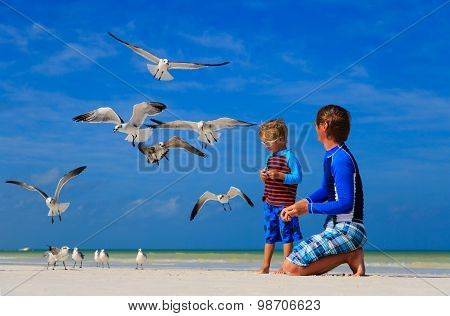 father and son feeding seagulls on beach