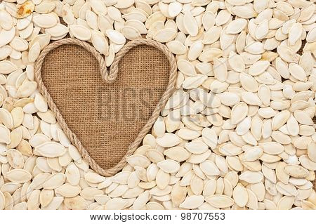 Symbolic Heart Made Of Rope Lies On Sackcloth And  Pumpkin Seeds