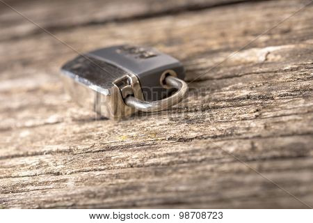 Security Concept - Metal Padlock Lying On Old  Wooden Table.