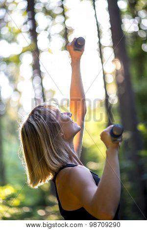 Woman Working Out Outdoors In Woodland