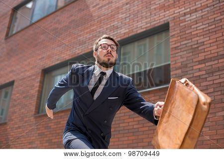 young businessman running in a city street