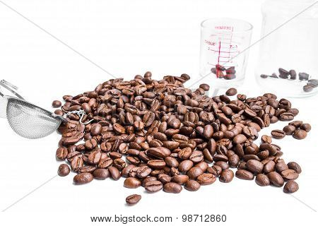 roasted coffee beans, strainer and glass jar and coffee shot glass