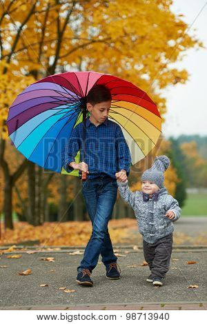 two brothers under rainbow umbrella