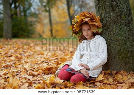 beautiful girl in autumn park with wreath of leaves