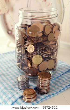 Coins in money jar on table close up