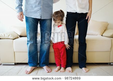 girl hugging mom and dad for legs