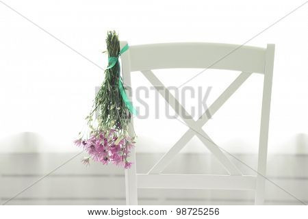 Bouquet of wild flowers drying on chair on light background