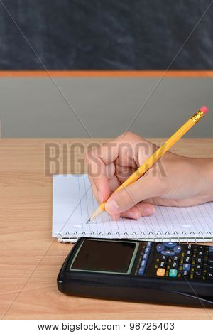 Closeup of a student taking notes. The girls hand is holding a pencil on a spiral notebook. A calculator is in the foreground and a chalkboard in the background out of focus.