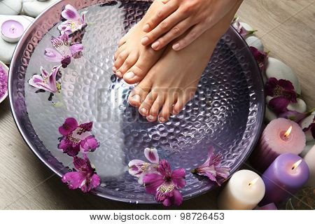 Female feet at spa pedicure procedure