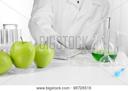 Scientist examines apples in laboratory