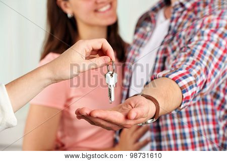 Real estate agent giving keys to young couple