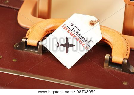 Suitcase with TRAVEL INSURANCE label, closeup