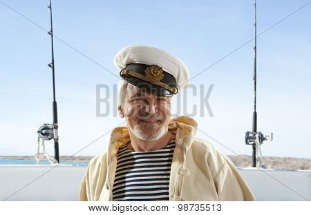 Captain. Happy sailor man on fishing boat background