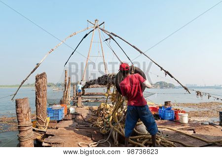 Unidentified Indian Fishermen Descend Their Chinese Fishing Net Into The Sea