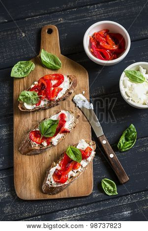 Toast With Feta Cheese, Red Roasted Peppers And Basil On A Dark Wooden Background