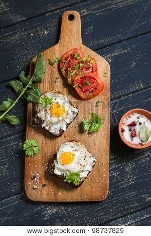 Toast With Feta Cheese And Fried Quail Egg, Fresh Tomatoes On A Dark Wooden Surface - A Healthy Brea