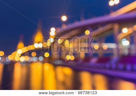 Blurred bokeh lights background, water reflection of suspension highway at twilight